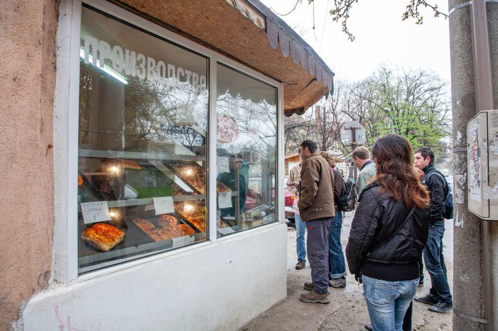 Наш новый друг помогает нам купить в этой маленькой пекарне баницу, популярную еду на завтрак. болгарская еда Традиционный болгарский путеводитель и 5 блюд, которые нельзя оставить без внимания! Banitsa and Baked Goods Shop 1 1024x682