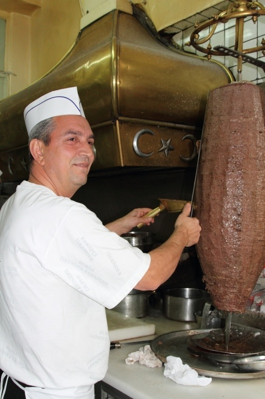 The chef is cutting the meat off the doner spit.