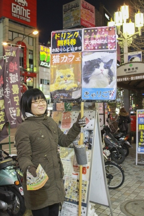 Cat cafés in Tokyo might be a little pricey, but this girl is very inviting as she holds her cat sign.
