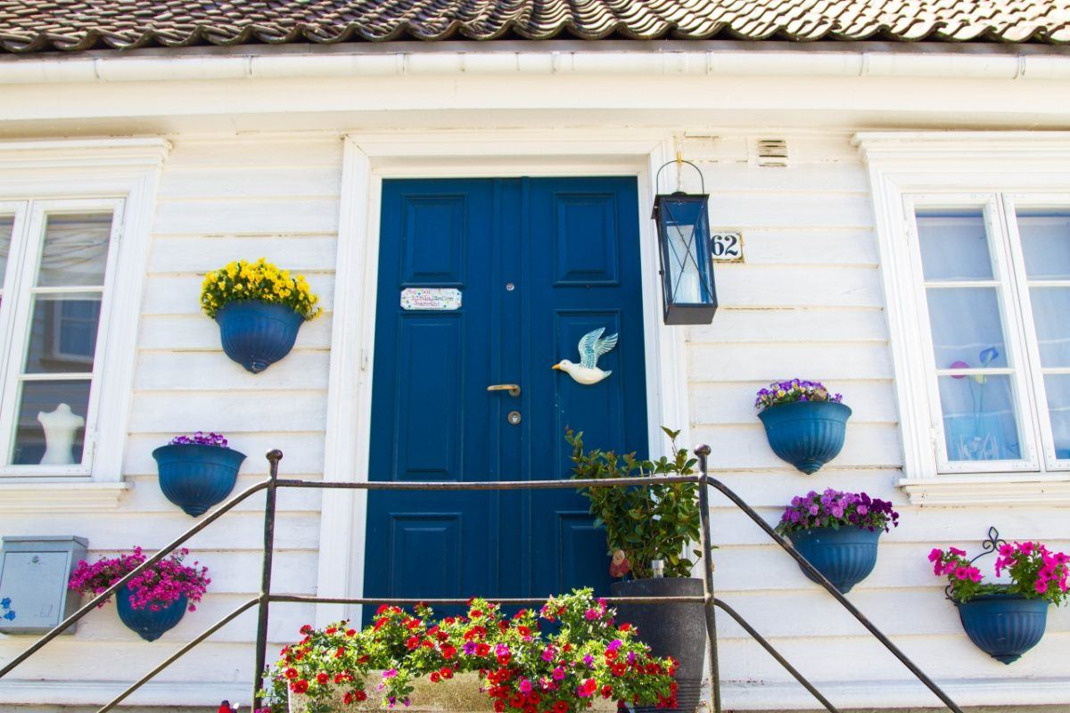 White house with blue door and blue flower pots in Gamle Stavanger