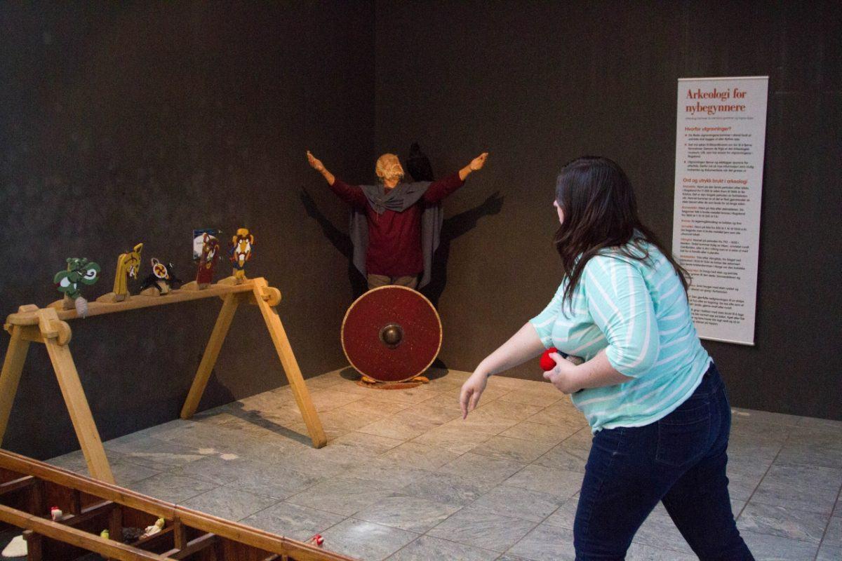 A girl throwing balls at toys