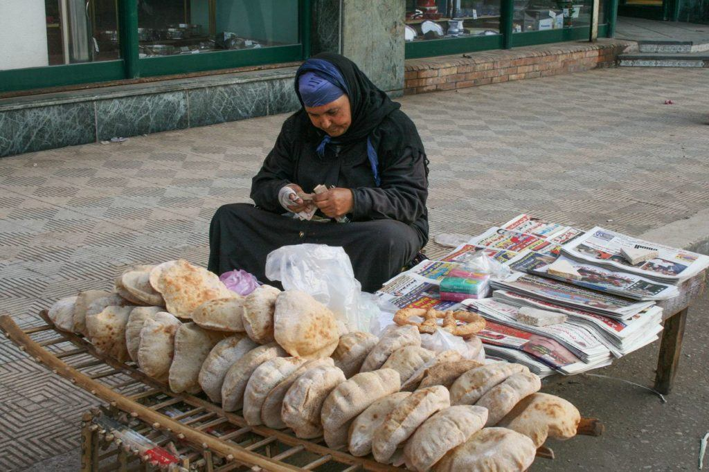 Bread and newspaper vendor selling early morning in Cairo.