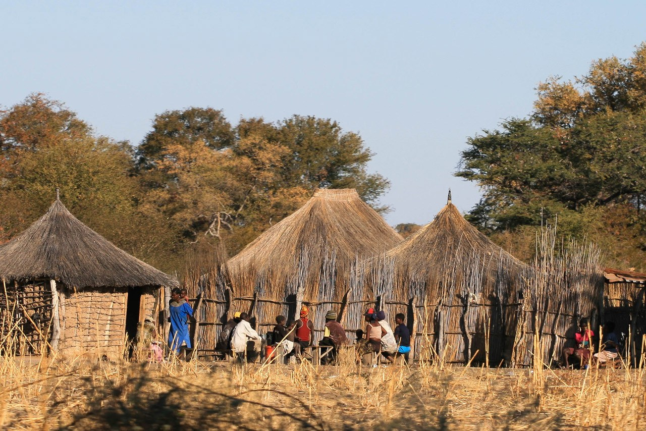 Namibian village with people sitting near thatched huts