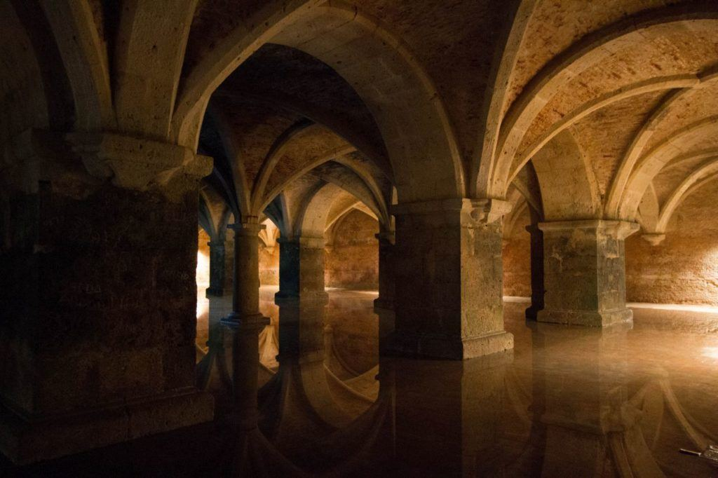 Underground cistern with stone pillars, rippling light, and sounds of dripping water in El Jadida, Morocco.