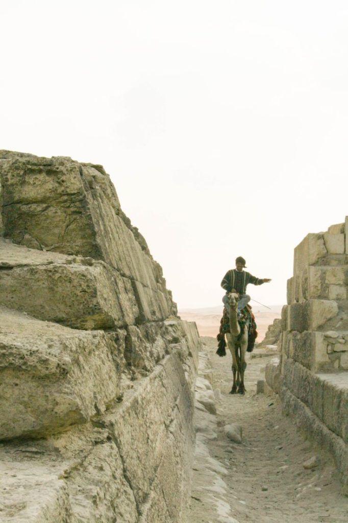Man riding camel through pyramids alley.