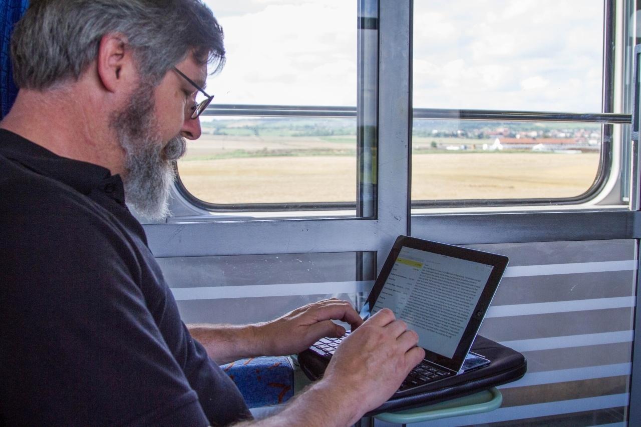 Jim working on his ipad on the train