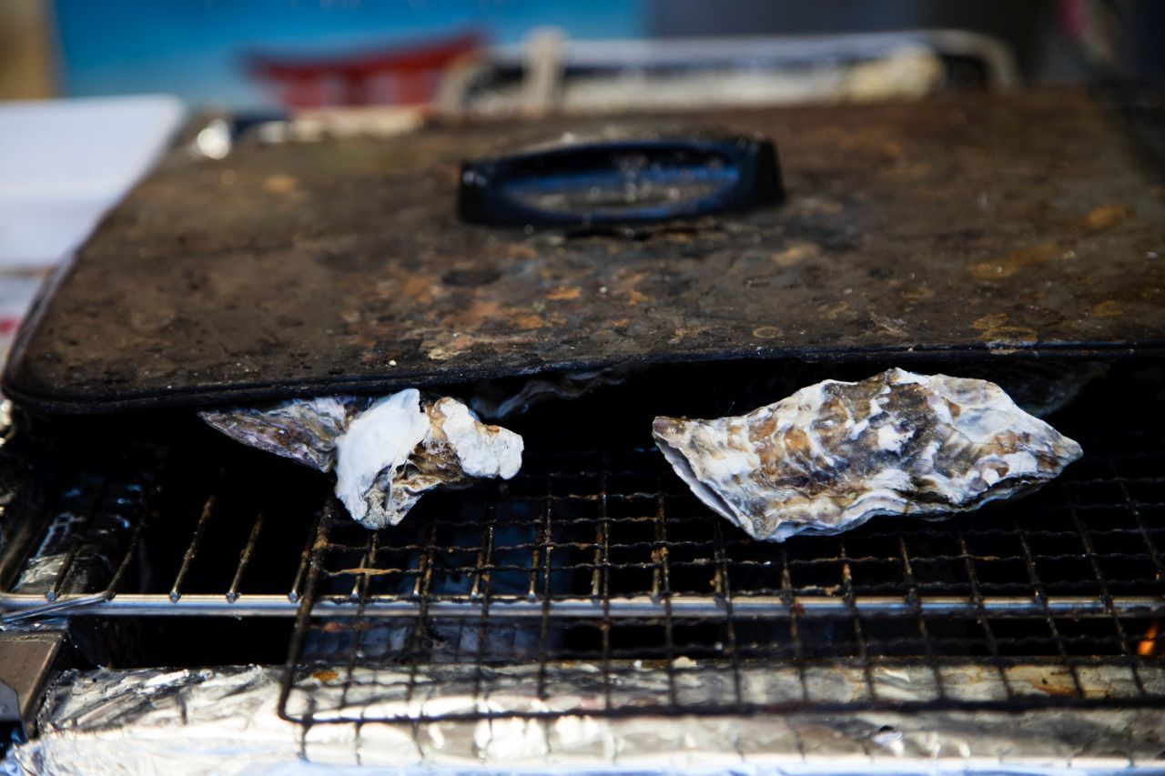 2 oysters being grilled
