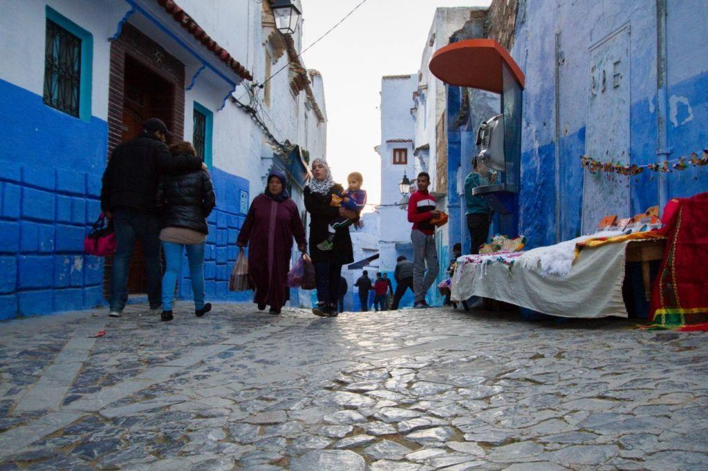 Families walking on a Chefchaouen street, buying dinner and other goods for the day.
