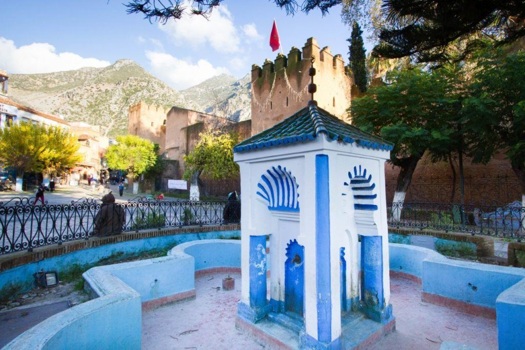 The main Kasbah, definitely a must-see on a one day trip to Chefchaouen. There is a blue fountain, the brown Kasbah, and the mountains.