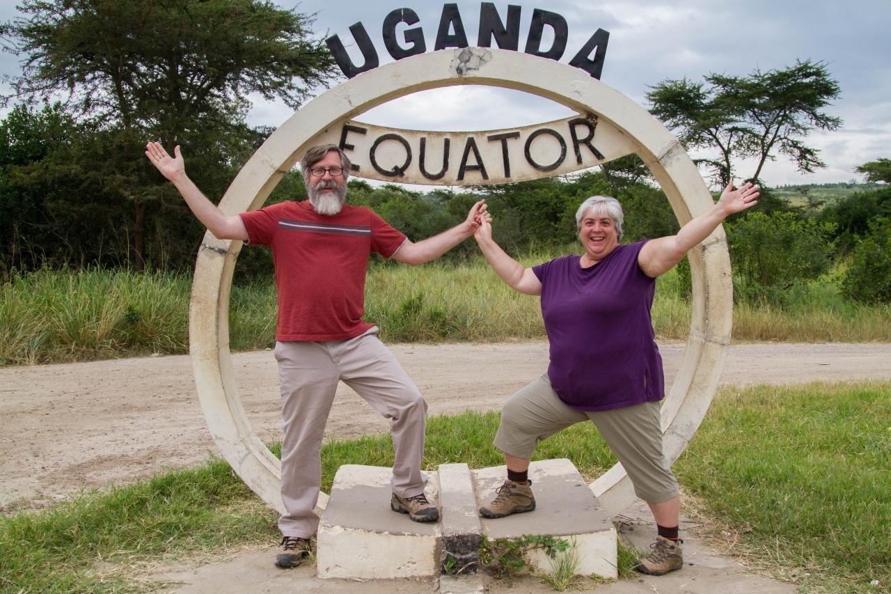 Happy travelers posing in front of the Uganda Equator Marker.