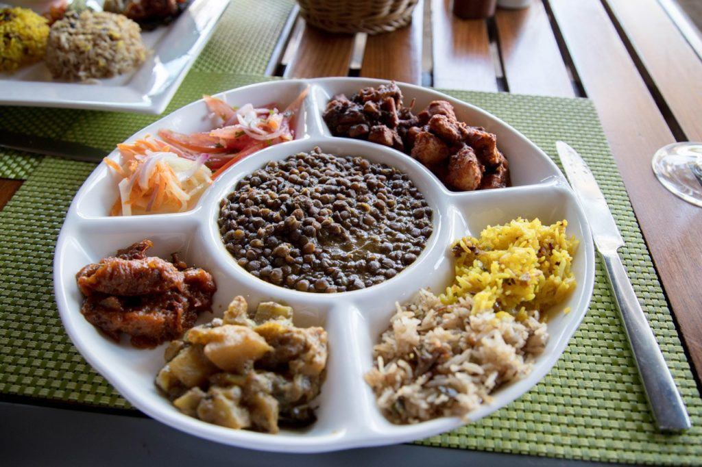 Traditional Mauritian taster plate with lentils, curries, and biryani.