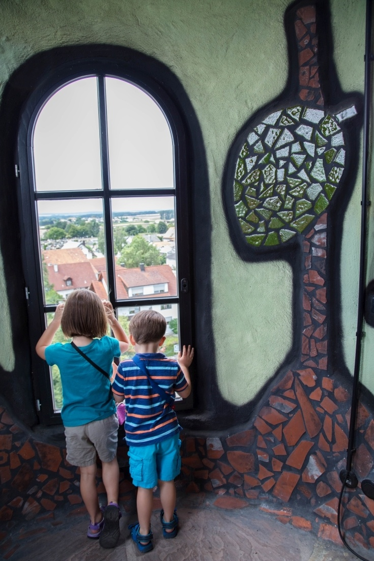 2 children gaze out of a window of the Kuchlbauer Tower