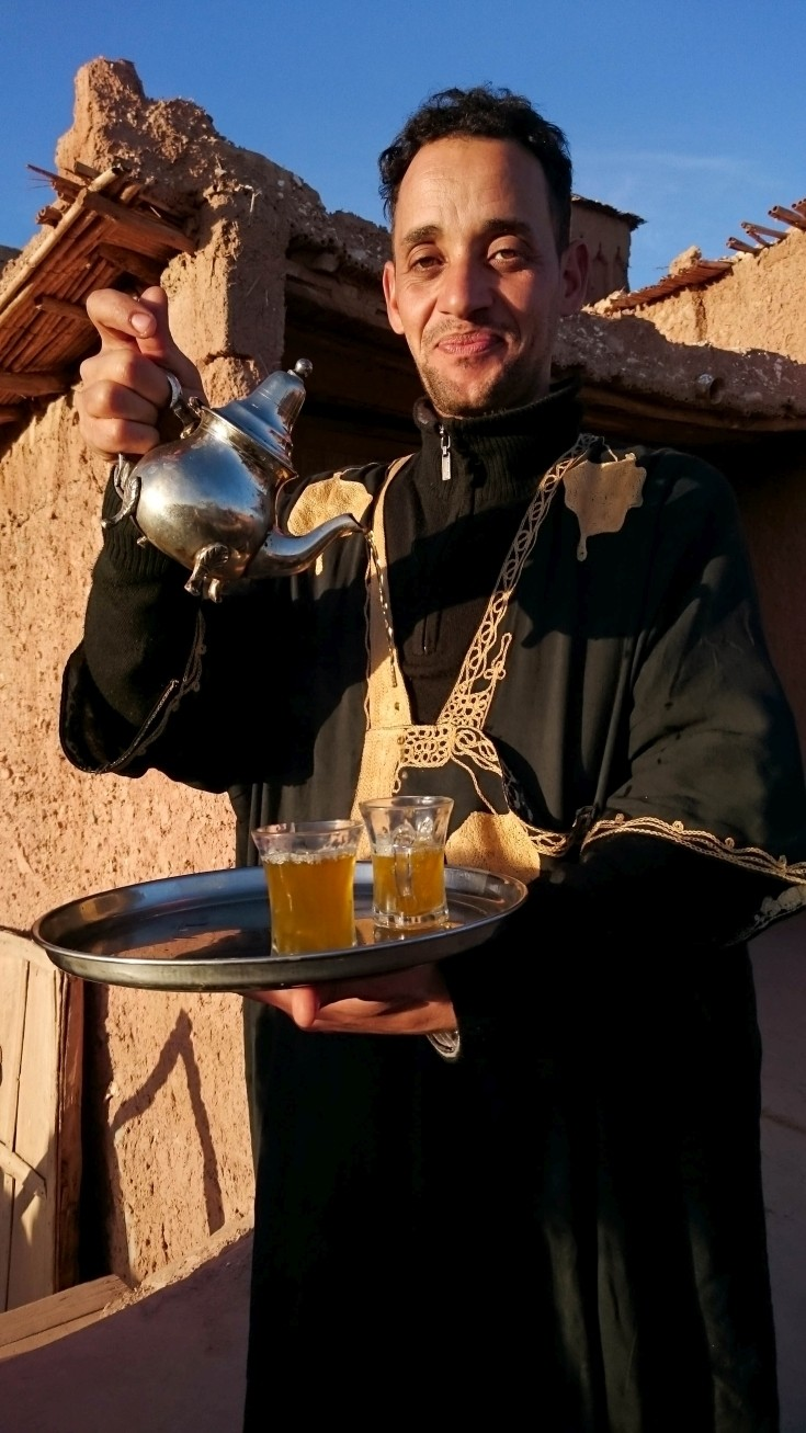 Moroccan waiter pouring two glasses of tea.