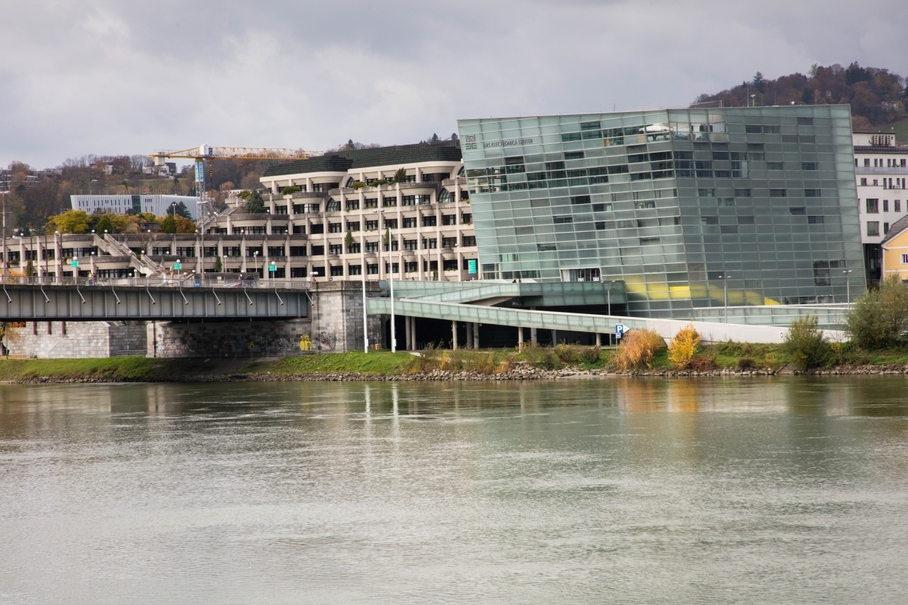 A Donau river and view of the opposite bank with one modern blue building, and one beige.
