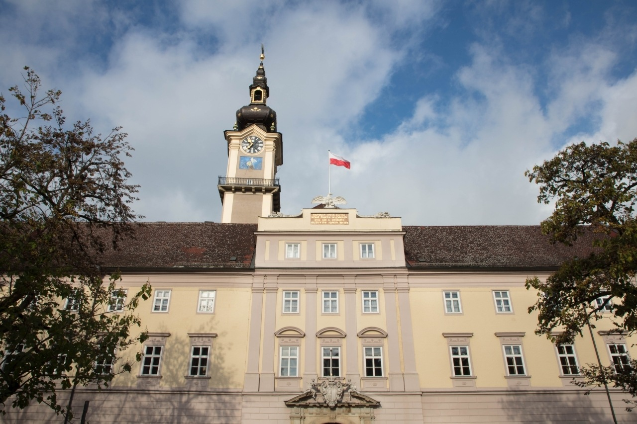 Large beige building with clock tower and Austrian flag
