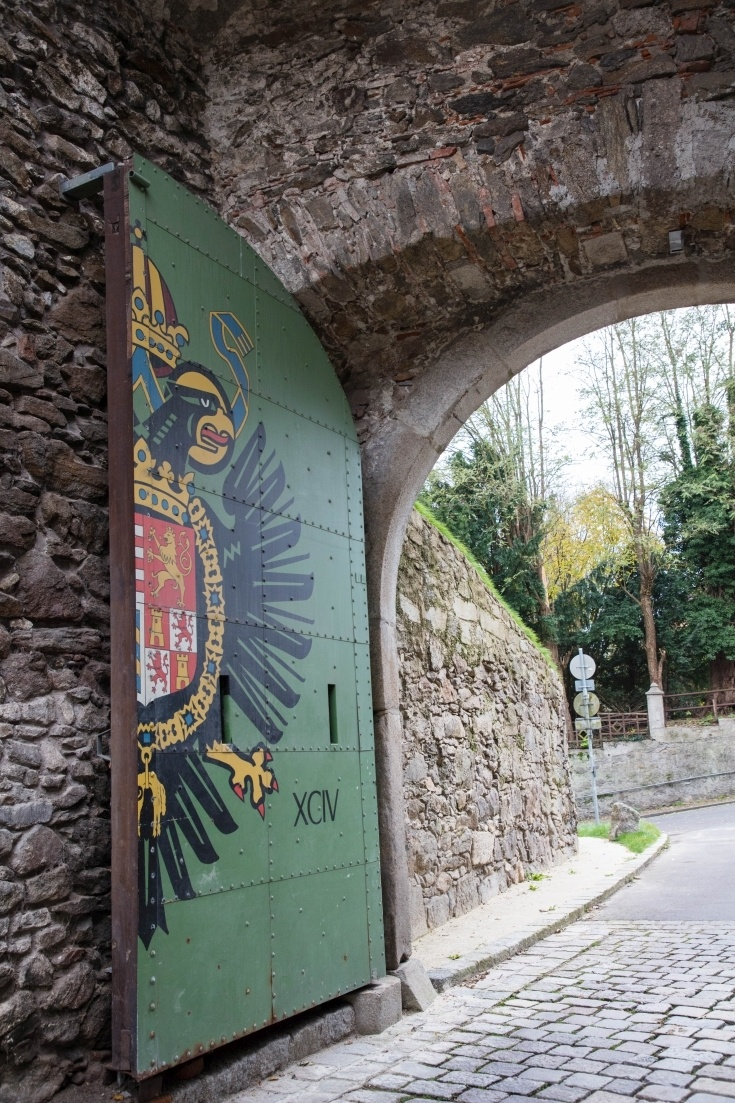 A stone archway filled with a half door painted green with an eagle on it.