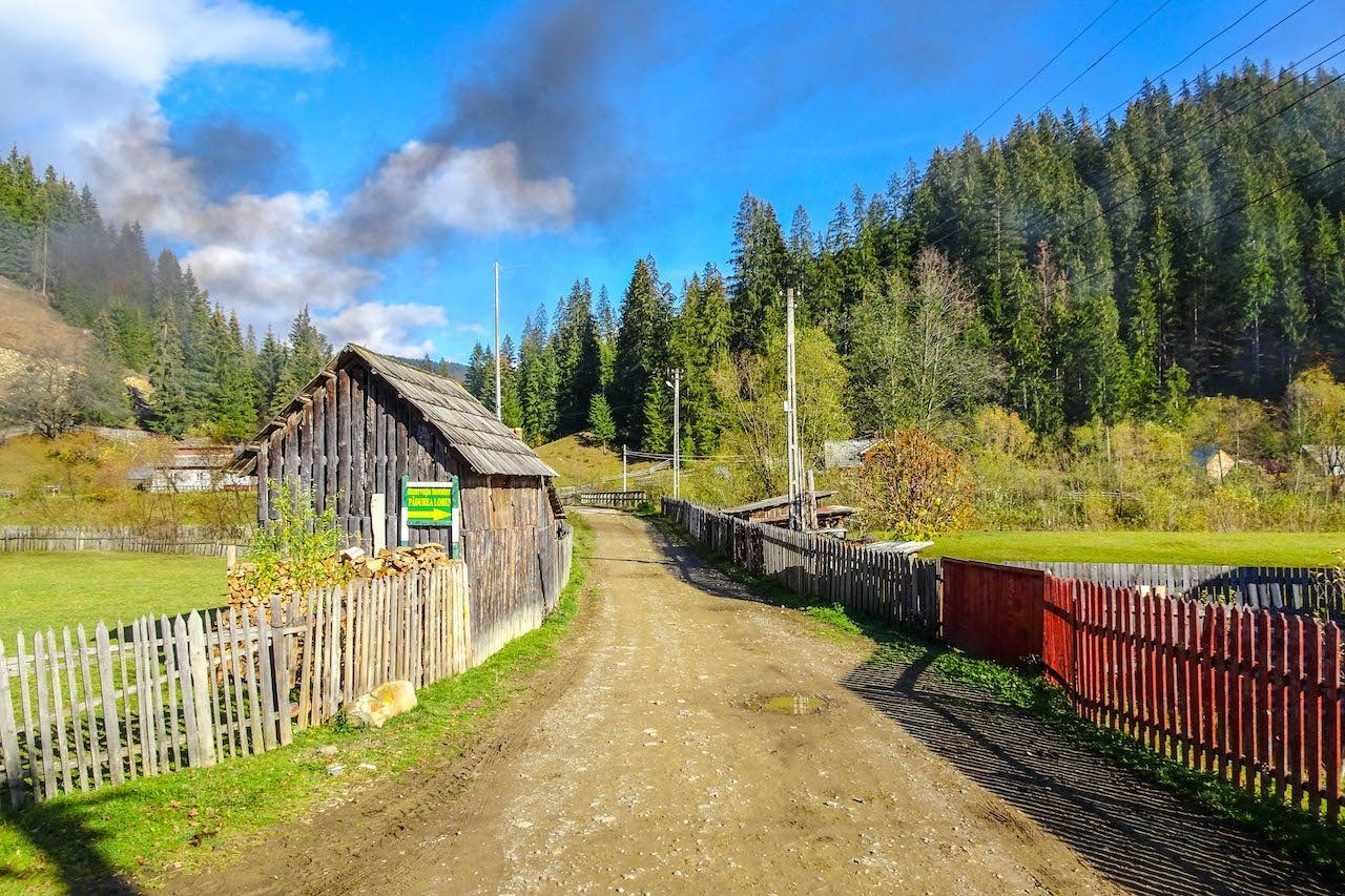 A dirt road and log cabin in Transylvania, Romania.