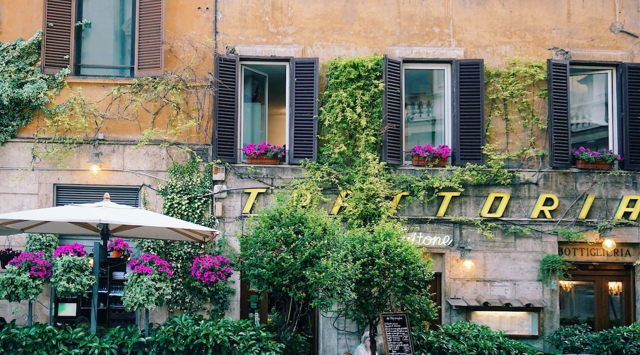 "A ""trattoria"" sign hidden by gorgeous spring flowers."