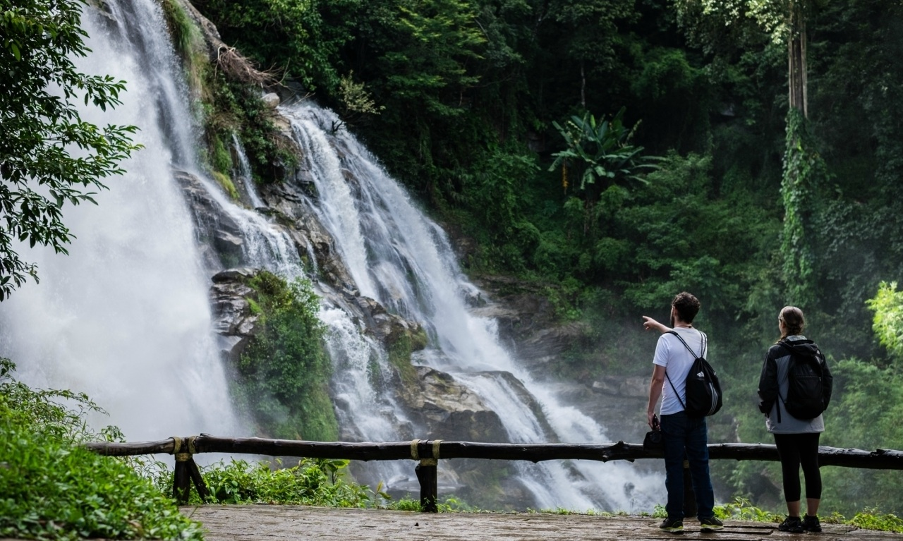 A couple stand in awe in front of a Thai waterfall.