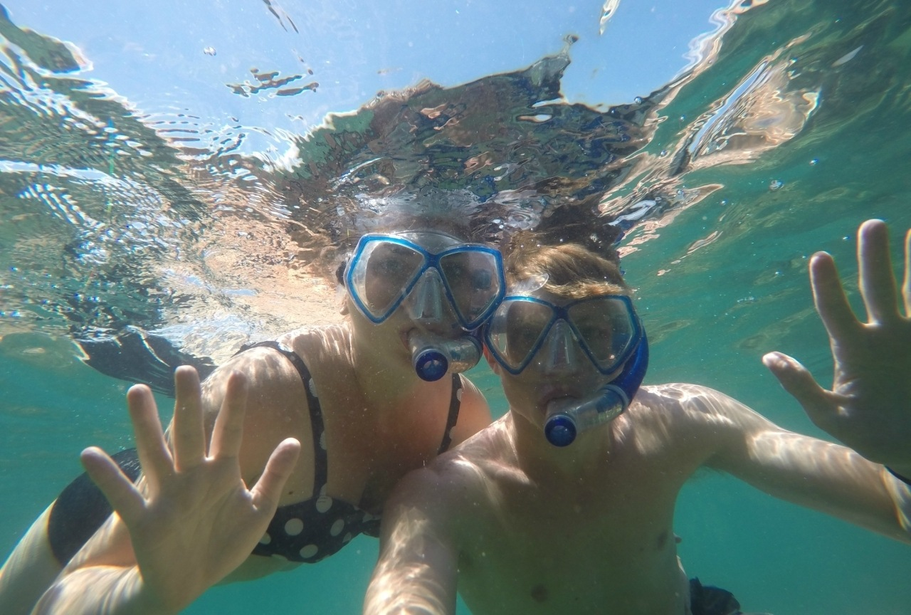 A couple looking at camera underwater with snorkels on