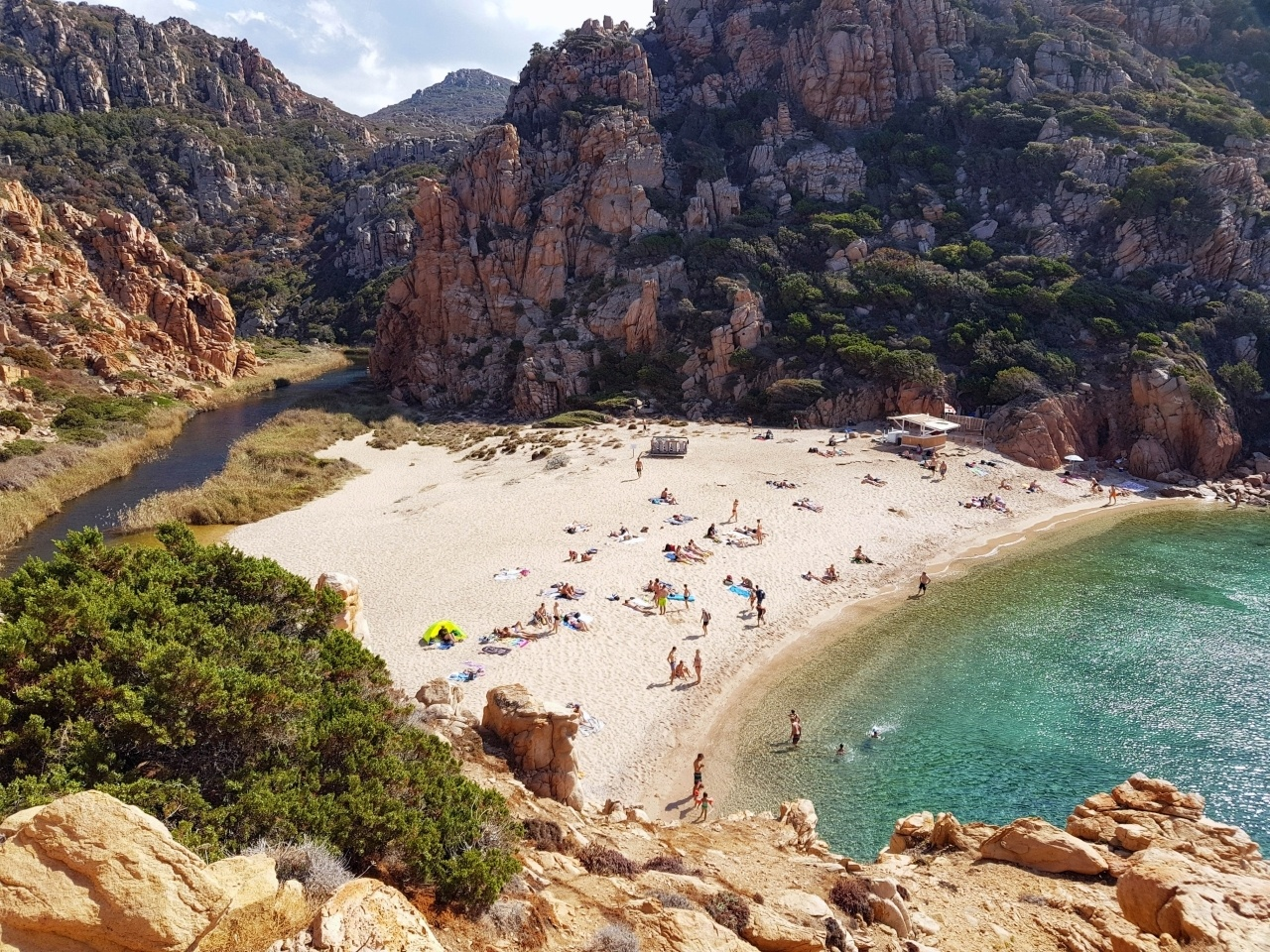 A beach with people in Sardinia.