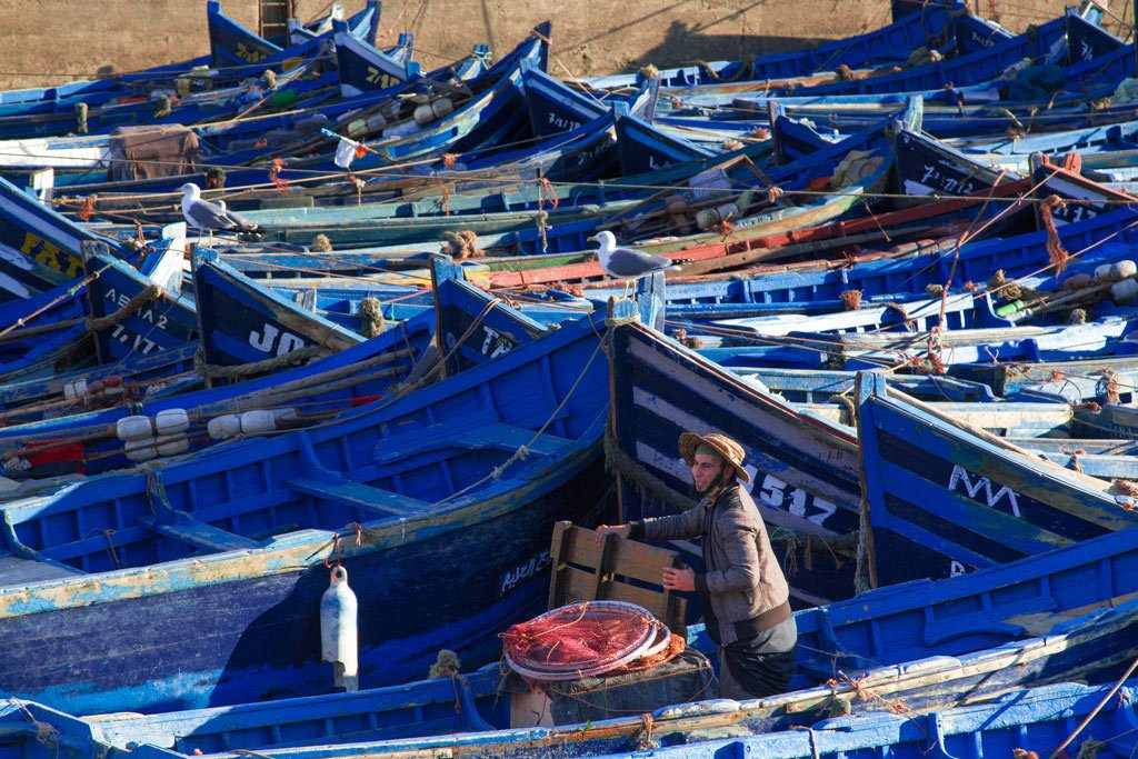 Fisherman and blue fishing boats are one of the things to do in Essaouira.