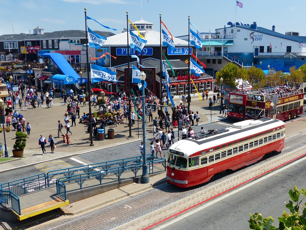 A red historic streetcar runs along the Embarcadero in San Francisco stopping at Pier 39