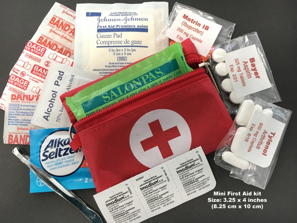 Contents of a tiny First Aid kit with Band-Aids, and a variety of non-prescription medications.
