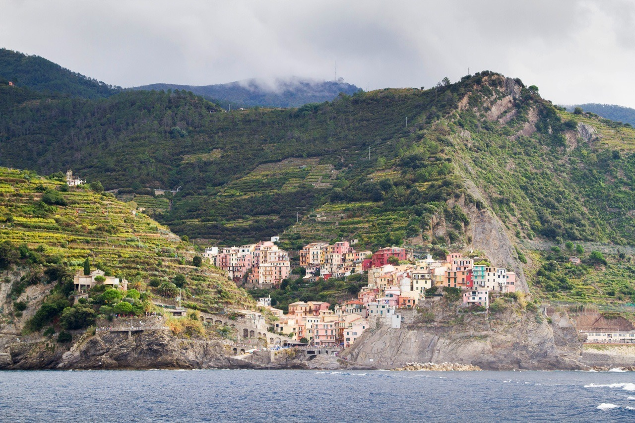 Taking a ferry past one of the five towns in Cinque Terre, Italy