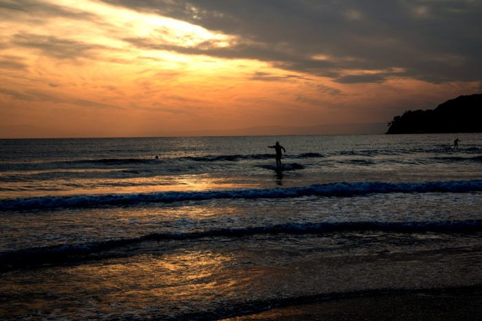 A sunset surfer, riding the waves at the Kamakura beach.
