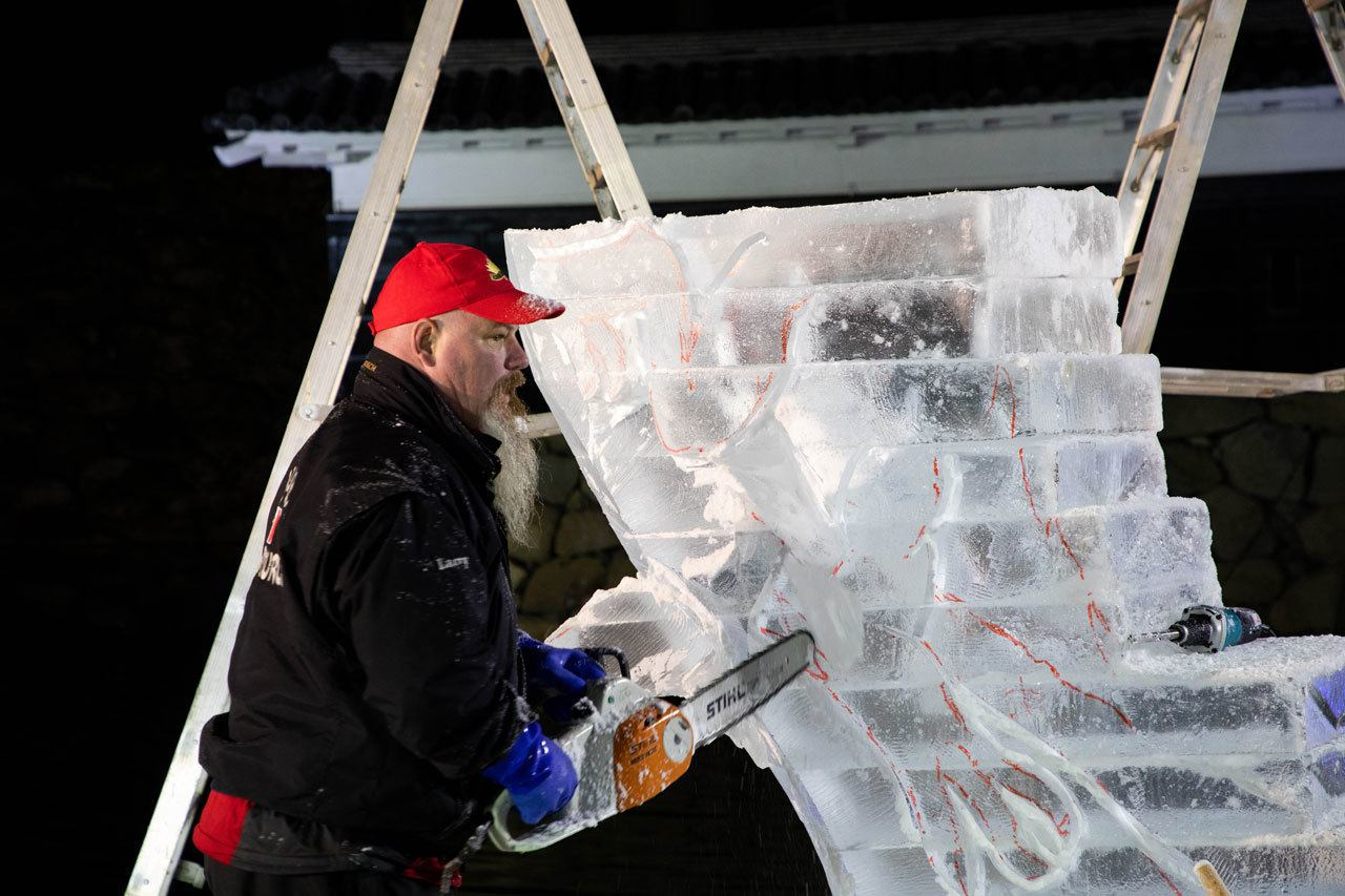 Canadian ice sculpture artist making some of the first cuts after the design is sketched on the ice block
