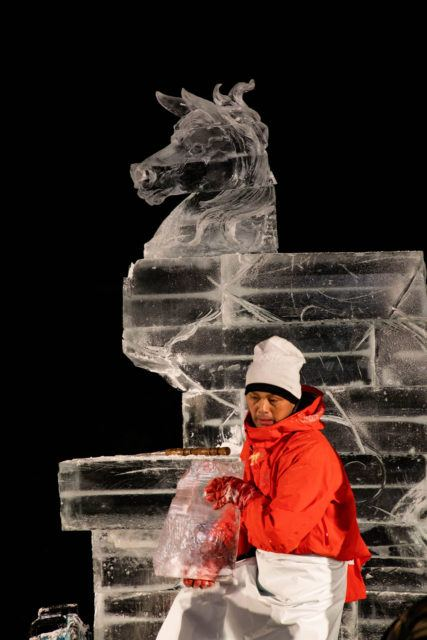 Artist taking off big chunks of ice before carving horse