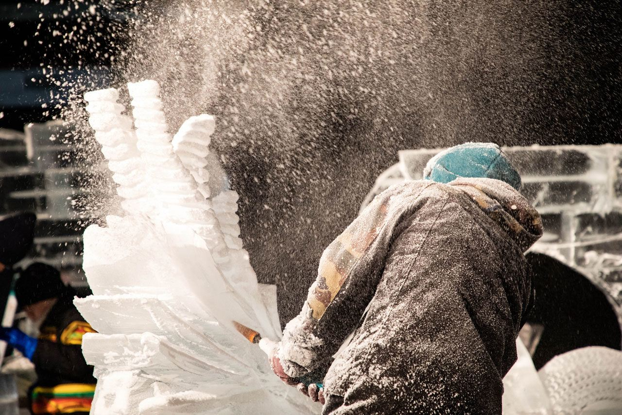Ice shards fly in a cloud as the artist chainsaws away