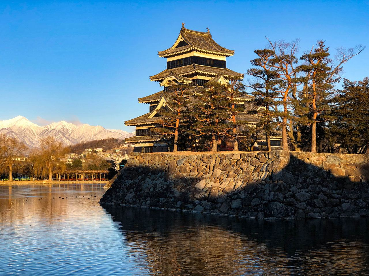 Matsumoto Castle with snow on Japanese Alps in background, a fantastic Japan winter destination