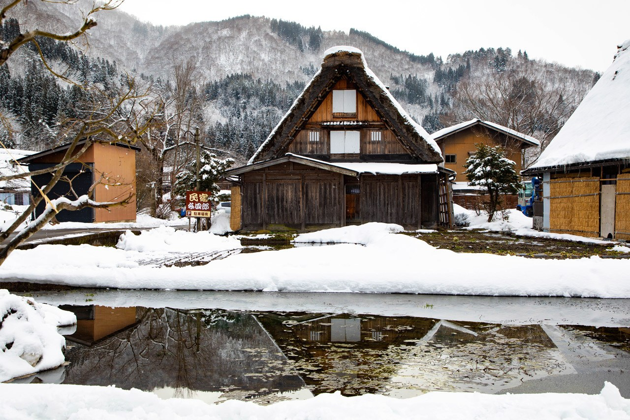 Snowy mountains in the background and a beautiful reflection of a gassho house (thatched roof) in the foreground, this is why we fell in love with Shirakawago.