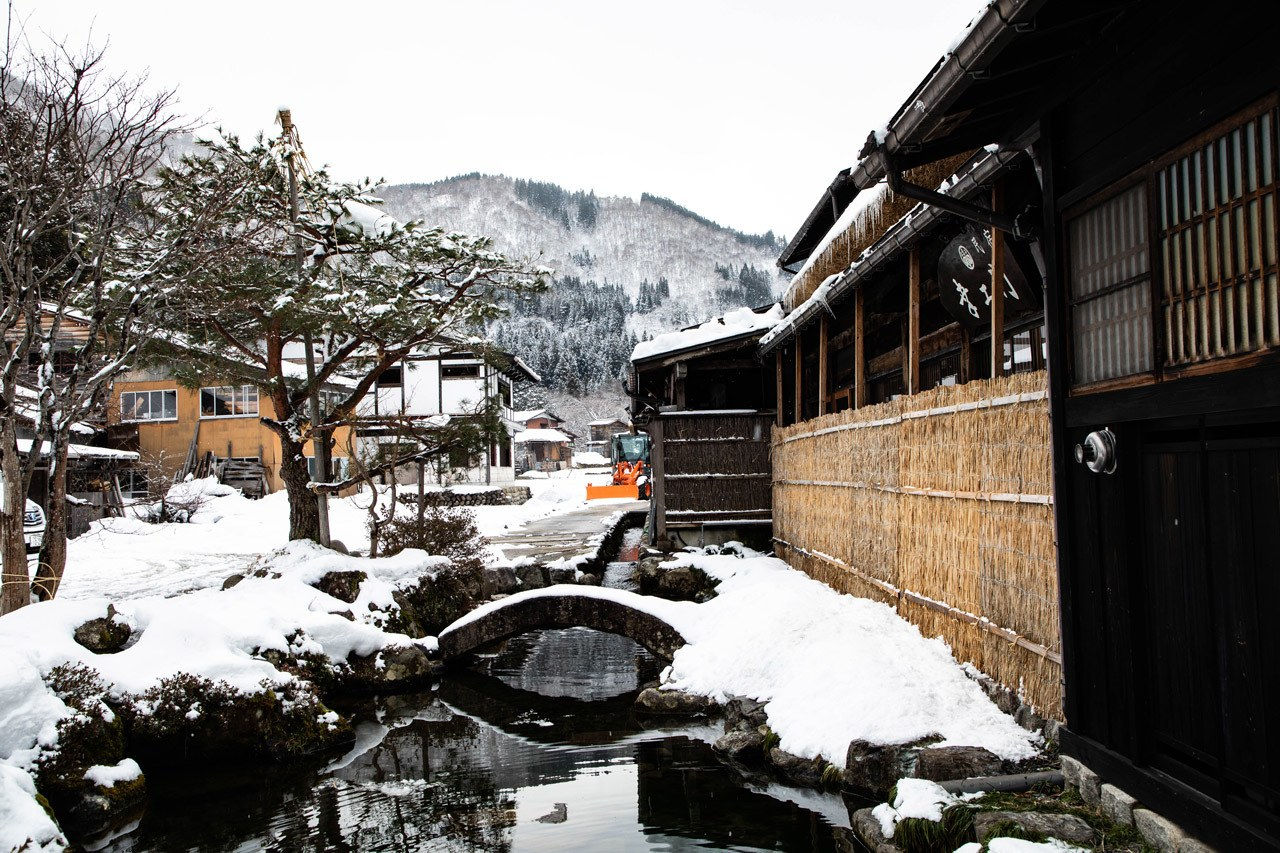 A small water canal and stone bridge next to one of the traditional houses in this world heritage Shirakawago village.