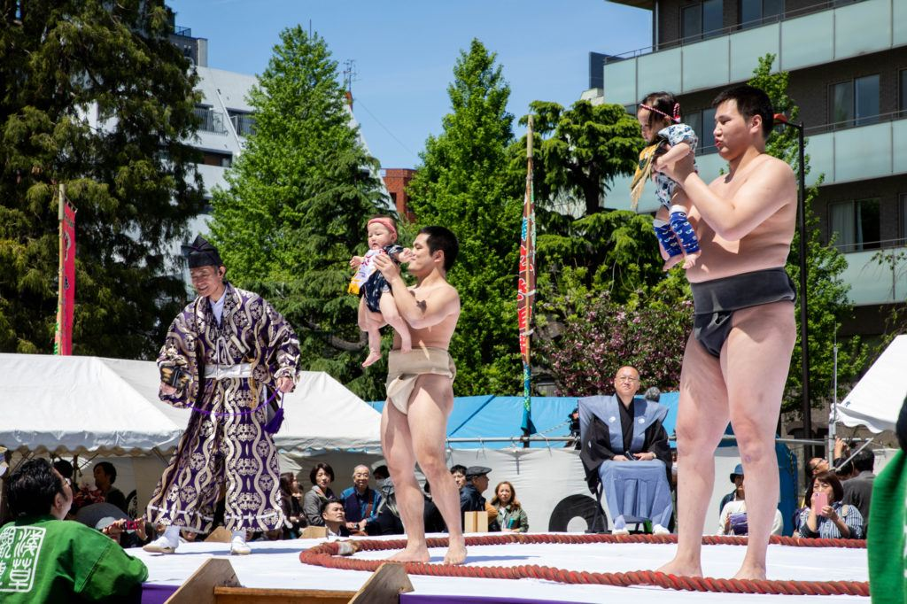 Young sumo wrestlers hold up 2 babies.