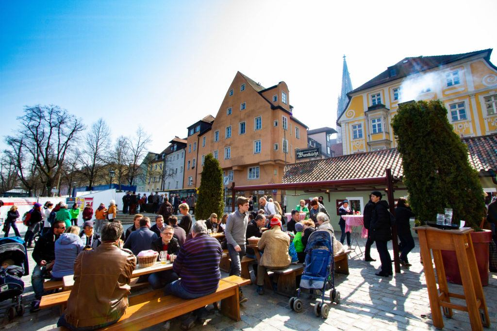 Посетители наслаждаются знаменитыми колбасками Вурсткухля.  Регенсбург, Германия Regensburg Germany 1 1024x682