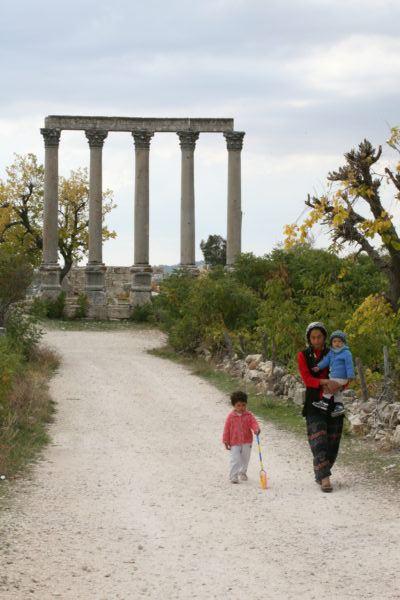 Zeus' Temple columns and a family walking in Uzuncaburç.