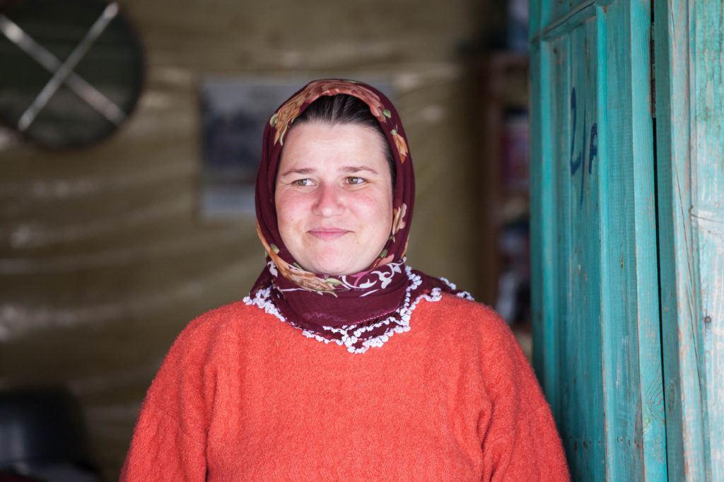 One of the village ladies standing in front of her blue door.