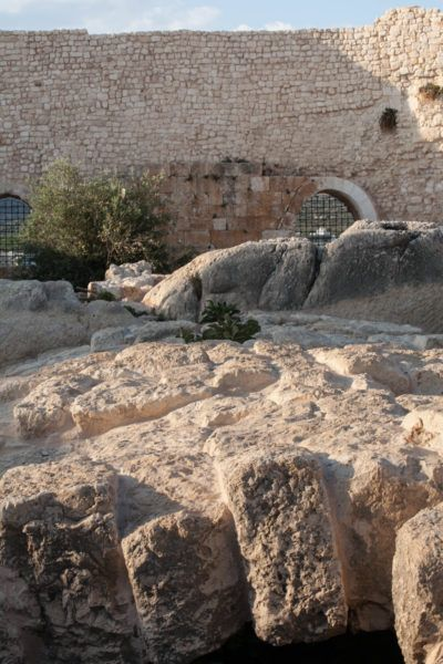 The ancient olive press stones and castle walls.