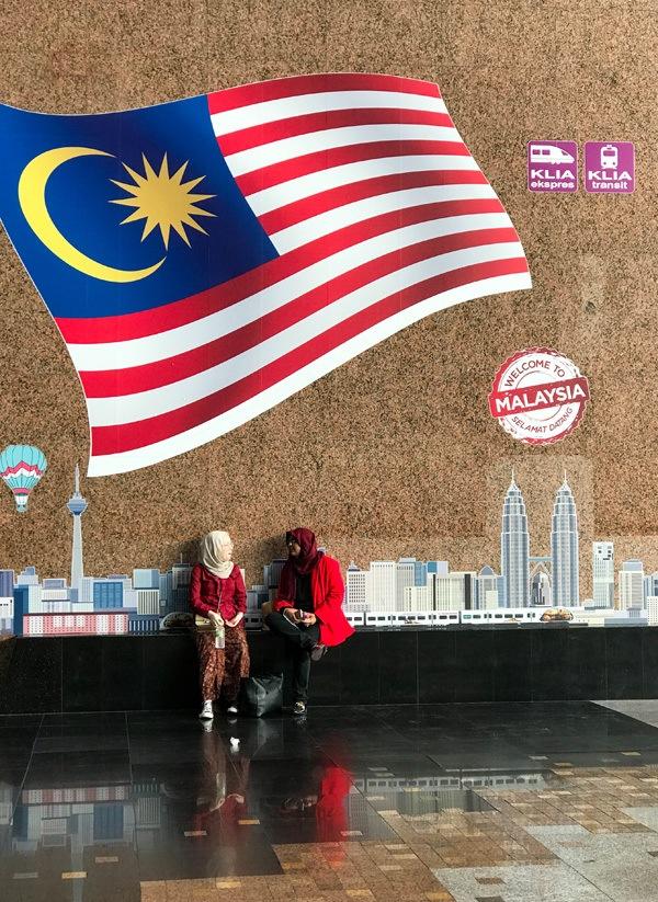Две женщины сидят под росписью Welcome to Куала-Лумпур