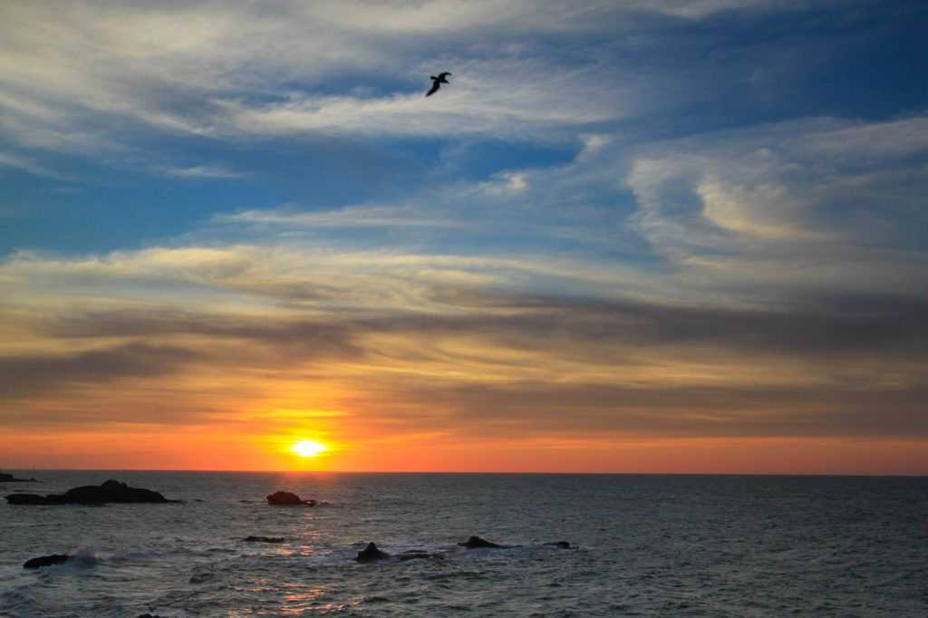 The sky above the Atlantic Ocean is painted yellow and orange as the sun sets in Essaouira.