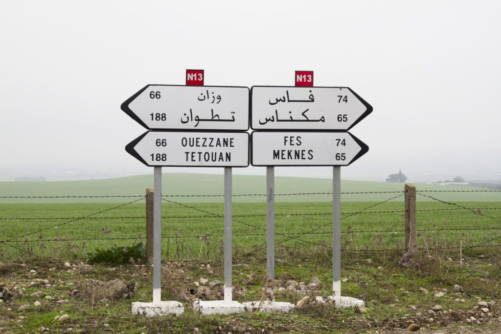A set of directional signs telling us which way to go in Arabic and in English.