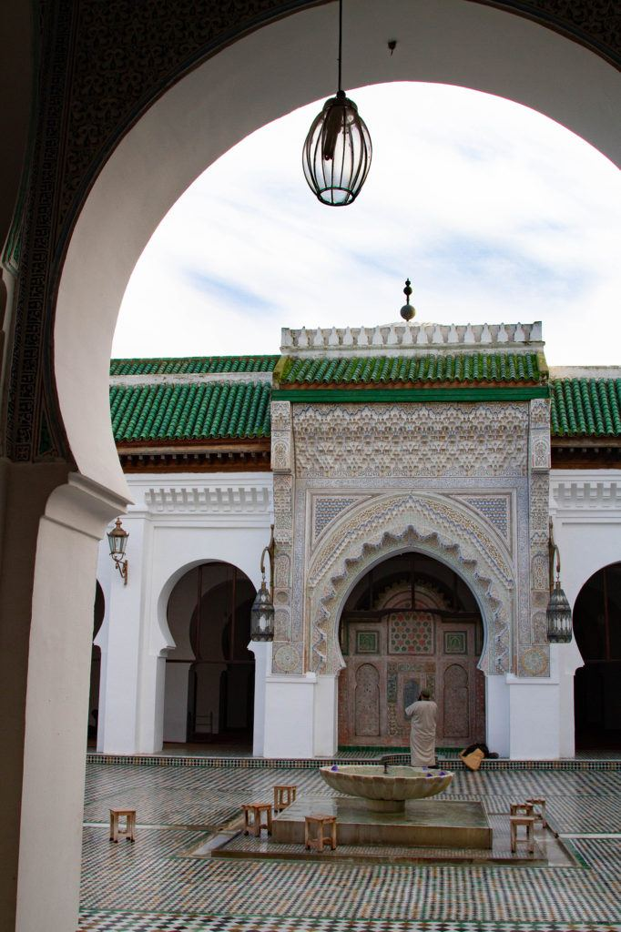 A silent glimpse into a madrasa in Fez, with its arch and tiles.