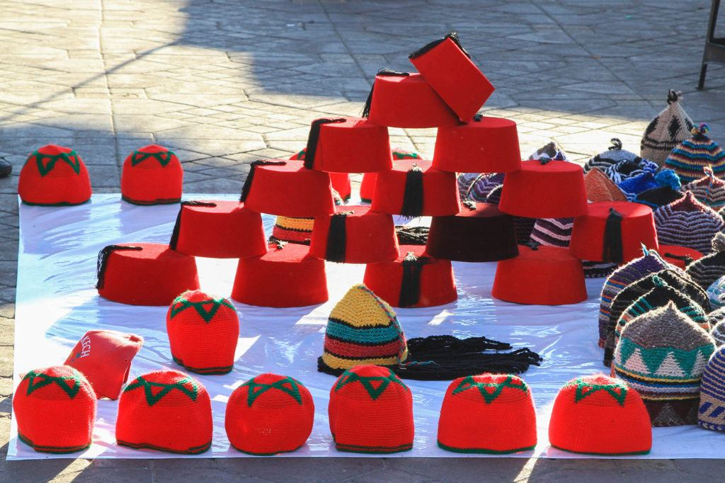 A vendo sells traditional red fez hats in the Jemaa el Fna market.