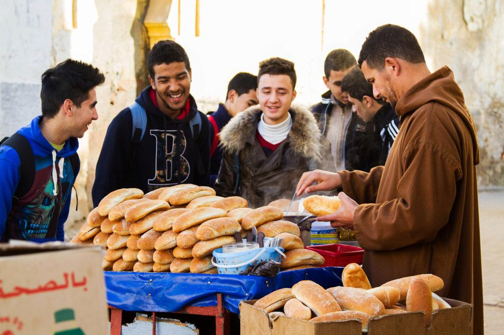 A group of teenage boys at a table stacked with small loves of bread waiting to be served by the vendor.