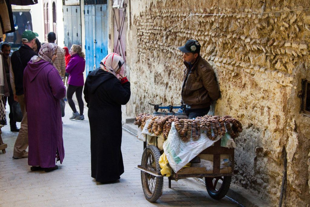 Two women stop to talk to a vendor selling dates in the Medina.
