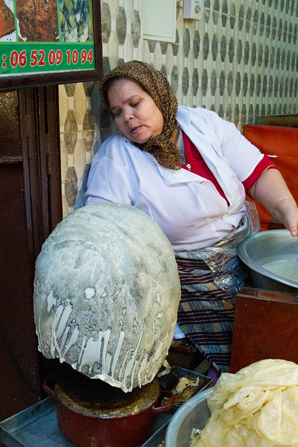 A lady makes thin bread by draping it of a ball.